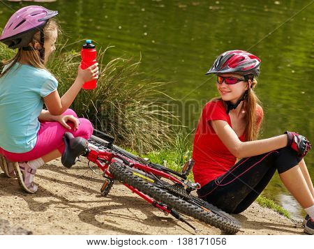 Bikes cycling children. Happy children rides bicycle. Children have rest near water in park. Bicycles are on coast. One child drink water.