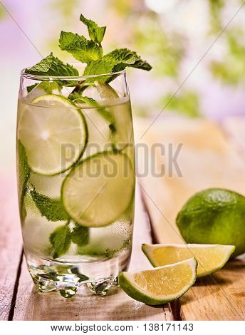 Alcohol drink. On wooden boards is glass with ice cubes alcohol drink . One drink number hundred seven cocktail mohito and two quartered lime with mint leaf. Country life. Outdoor. Light background.