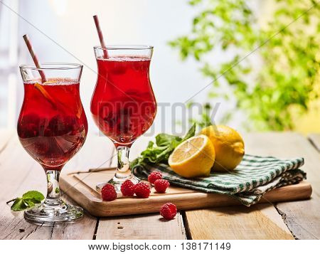 On wooden boards are ice cold cocktail two glasses with red berries lemon cocktail . Alcohol country cocktail beverage number hundred thirty one with leaf mint. Outdoor cocktail beverage .