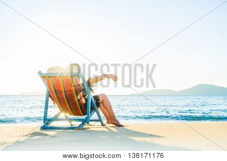 Woman relaxing in deck chair on the beach on a sunny day