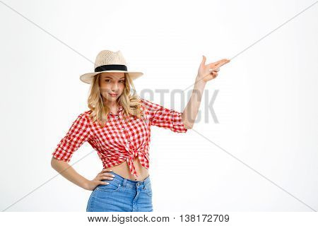 Portrait of young beautiful country girl in hat, jeans and shirt smiling, looking at camera, pointing fingers in side over white background. Copy space.