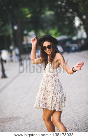 Young pretty woman outdoor fashion portrait. Beautiful girl in summer dress and sunglasses dancing on the street