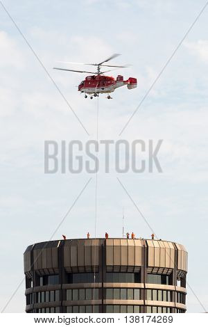 BASEL, SWITZERLAND - JULY 11, 2016: Heliswiss International AG performing equipment air lift for maintenance on rooftop of the Bank for International Settlements headquarters in Basel, Switzerland.