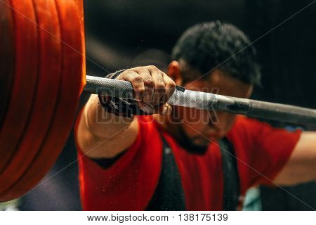 male powerlifter preparing for squats with a barbell during competition of powerlifting