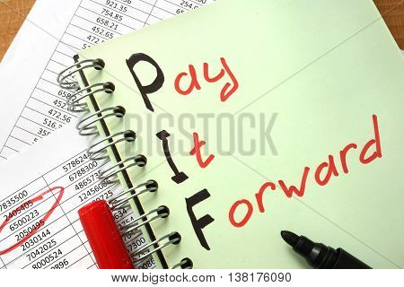 Notebook with  sign Pay It Forward PIF and charts.