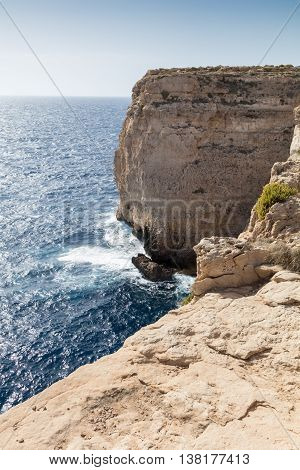 Waves smash against massive cliffs towering above the blue mediterranean sea