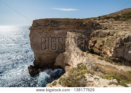 Waves smash against massive cliffs towering above the blue mediterranean sea dwarfing a lone figure. Landscape
