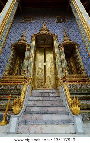 Bangkok, Thailand - June 30, 2016: Beautiful golden doors and naga serpents at the entrance to the Phra Mondop library at Thailand's Grand Palace