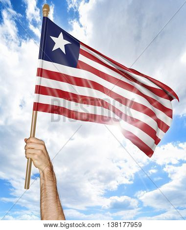 Person's hand holding the Liberian national flag and waving it in the sky, 3D rendering