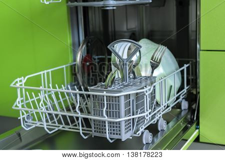 Clean dishes in the dishwasher on a background of green furniture