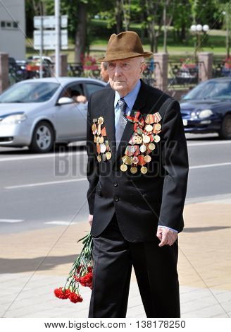 Molodechno, Belarus - July 3, 2014: World War II veteran with medals and awards walking along street with red carnations. Independence Day in Belarus in 2014.