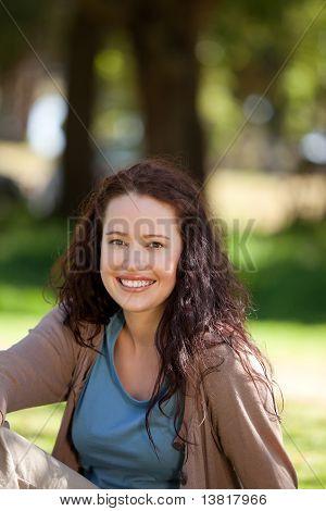 Schöne Frau im Garten sitzen