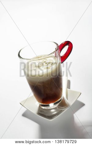 Fresh coffee in a tall glass with cream close up