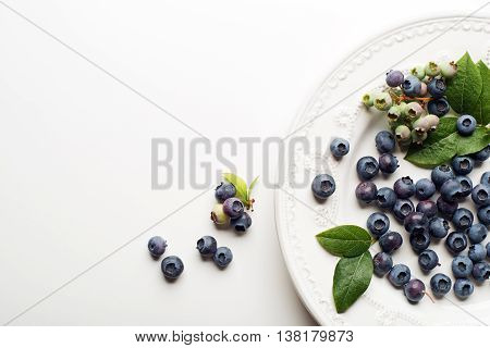 Juicy and fresh blueberries with green leaves on white background