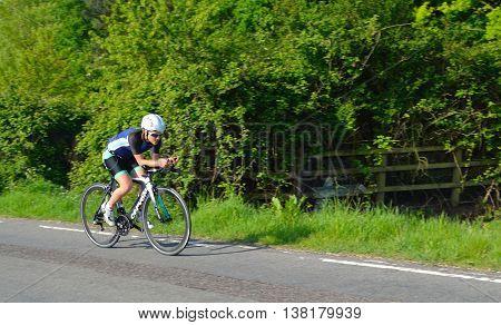 Grafham, Cambridgeshire, England - May 22, 2016:  Female triathlon  competitor on road cycling stage.