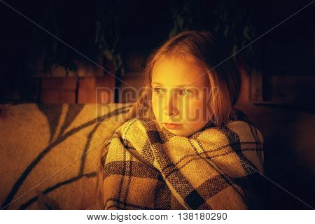 Lonely teenager in warm blanket sitting on a sofa.
