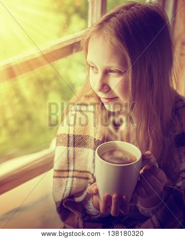 Young beautiful girl in a village house with a cup of coffee.