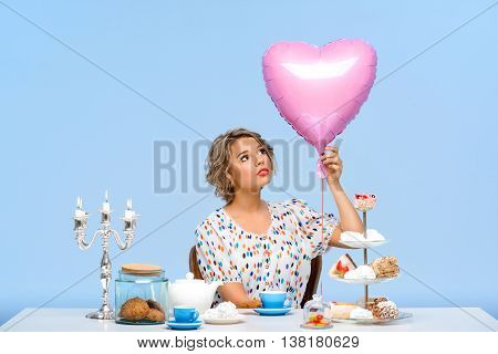 Portrait of young beautiful girl in white blouse sitting at table with sweets, holding pink baloon in shape of heart over blue background.