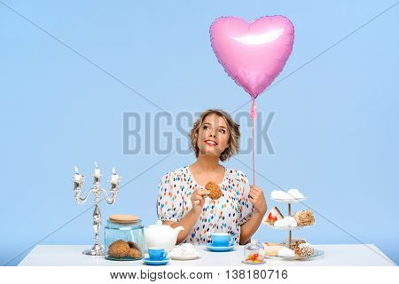 Portrait of young beautiful girl in white blouse sitting at table with sweets, smiling, holding baloon and cookie over blue background.
