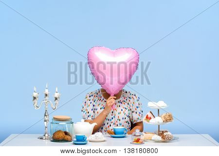 Portrait of young beautiful girl in white blouse sitting at table with sweets, holding pink baloon in shape of heart instead of head, over blue background.