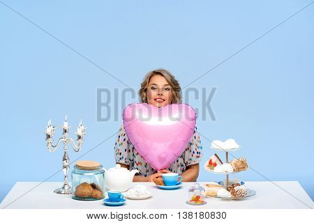 Portrait of young beautiful girl in white blouse sitting at table with sweets, smiling, looking at camera, holding pink baloon in shape of heart, over blue background.