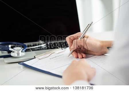 Close up view of female medicine doctors hands filling patient medical form. Physician working with paper in hospital office room. Therapeutist sitting at working table making some paperwork
