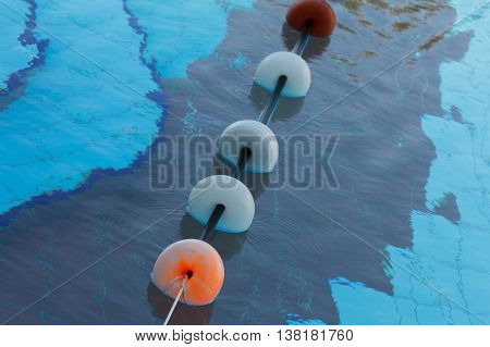 Clean blue water of the swimming pool with buoy
