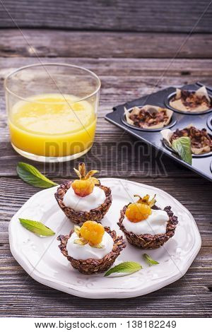 Healthy breakfast. Homemade granola cup with yogurt and fresh cloudberries on a simple wooden background on a ceramic plate. selective focus