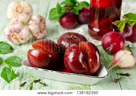 Pickled plum with garlic in glass jar. Home canning