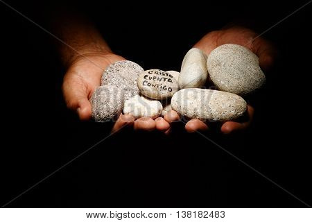 Praying hands with a rocks symbol religious