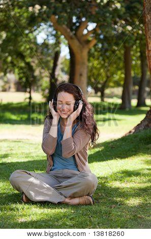 Mujer escuchando música en el jardín