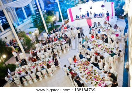 Blured Effect Of Guests At Their Table On Wedding Party