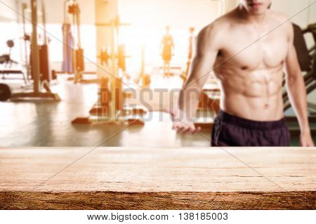 Wooden desk space over fitness gym and man open hand to empty desk. For product display montage. Business presentation.
