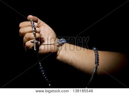 Praying Hands with rosary in black background