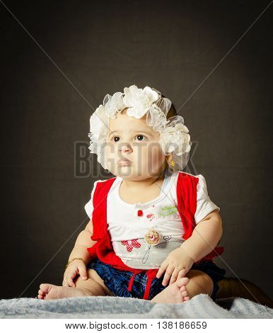 Small girl sitting on bright blanket isolated from textured background