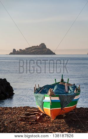 Mediterranean seascape: fishing boat and lava stack in the background