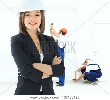 Woman construction worker with hard hat with staff on background