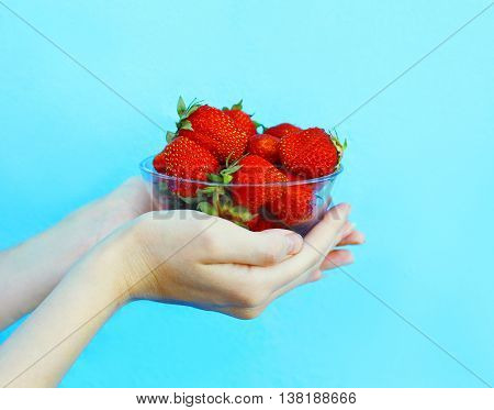 Female hands holding handful of strawberries close up over blue background