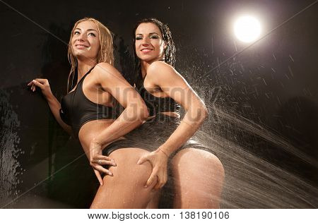 two sexy brunette and blond models women standing against a wall in a black bikini on black background in water studio. Water drops on woman body.
