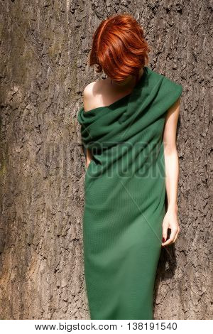 Red-headed woman in green dress against giant oak tree. Outdoor photo at bright sunny day