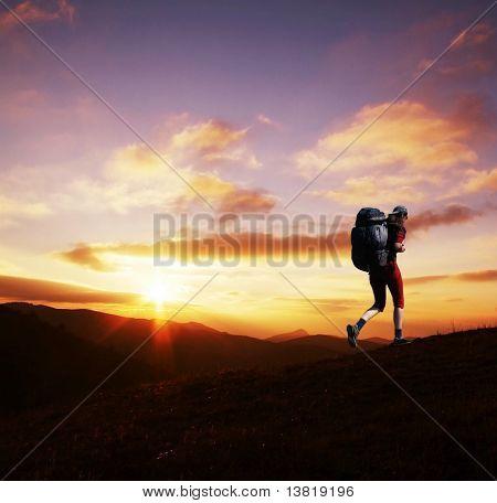 Girl going along hill on sunset