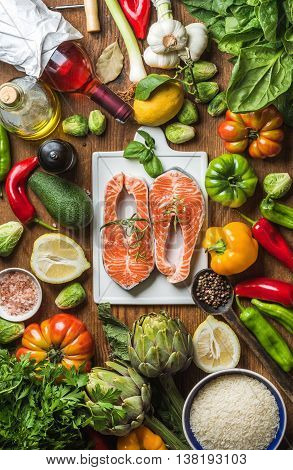 Dinner cooking ingredients. Raw uncooked salmon with vegetables, rice, herbs, lemon, artichokes, spices and bottle of rose wine on white ceramic board over wooden background, top view, vertical composition