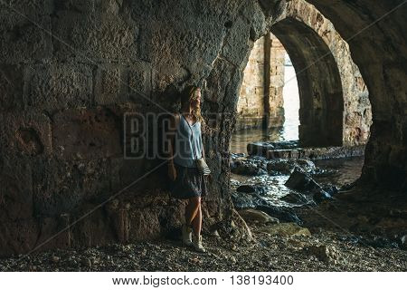 Young blond tourist woman stading in ancient stone shipyard and looking at the sea in the Old city, Alanya, Meditarranean region, Turkey.