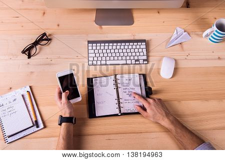 Businessman at the desk, wearing smart watch, working on smart phone. Personal organizer, computer and various office supplies around the workplace.