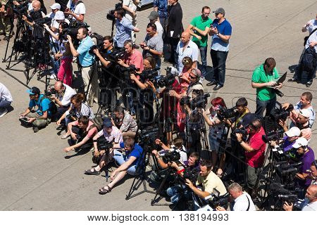 Odesa, Ukraine - July 03, 2016: correspondents and cameramans on the docks of Odessa seaport during celebration Ukrainian NAVY day and the warships at the background