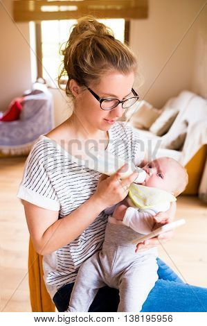 Beautiful young mother holding her baby son in the arms, feeding him with milk from bottle, working on smart phone