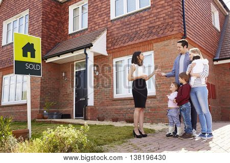 Young Family Collecting Keys To New Home From Realtor
