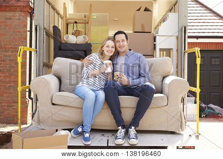 Couple With Sofa On Tail Lift Of Removal Truck Moving Home