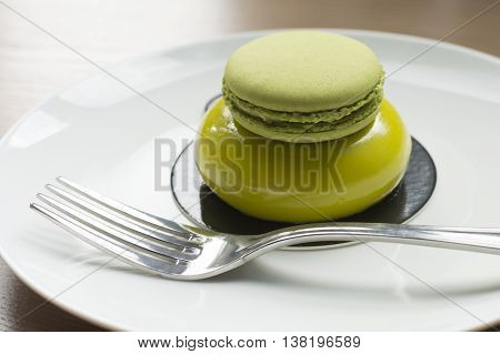 close up of green dessert with macaron and fork on white plate standing on table