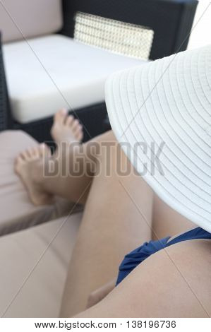 woman in blue beachwear and white hat lying on lounge with legs spread out. Woman face completely covered with hat.